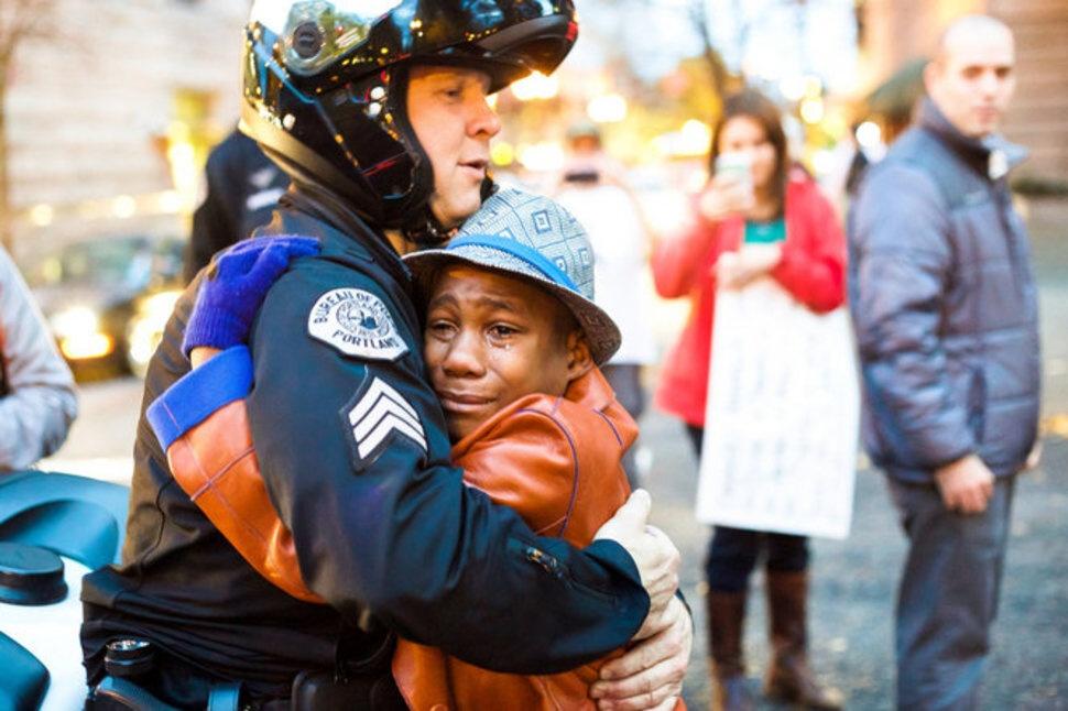 Bret Barnum objíma 12-ročného Devona Harta, po streľbe na Michaela Browna na demonštrácii. November.