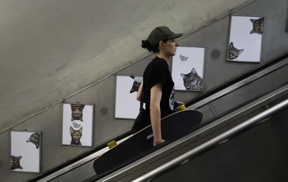 KK19 Londýn - Na snímke cestujúca prechádza okolo obrázkov s maèkami na stanici metra Clapham Common v Londýne 13. septembra 2016. Za nápadom vymeni reklamy za obrázky s maèkami stojí obèianske združenie Citizens Advertising Takeover Service (CATS). Financie na prenájom všetkých reklamných plôch sa vyzbierali prostredníctvom crowdfundingovej služby Kickstarter. Na 23 000 britských libier (27 000 eur) sa zložilo takmer 700 ¾udí. FOTO TASR/AP A woman travels on the escalator passing portraits featuring cats, on display, at the Clapham Common Tube station in London, Tuesday, Sept. 13, 2016. Cat lovers in need of a pick-me-up may start gravitating toward London's Clapham Common Tube station. All of the station's customary advertisements have been taken down, replaced by 68 oversized portraits of rather adorable cats. (AP Photo/Frank Augstein)