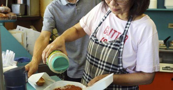 Belinda Lauová, manažérka honolulskej reštaurácie, sype syr na špagety, ktorý sú v plastovom obale